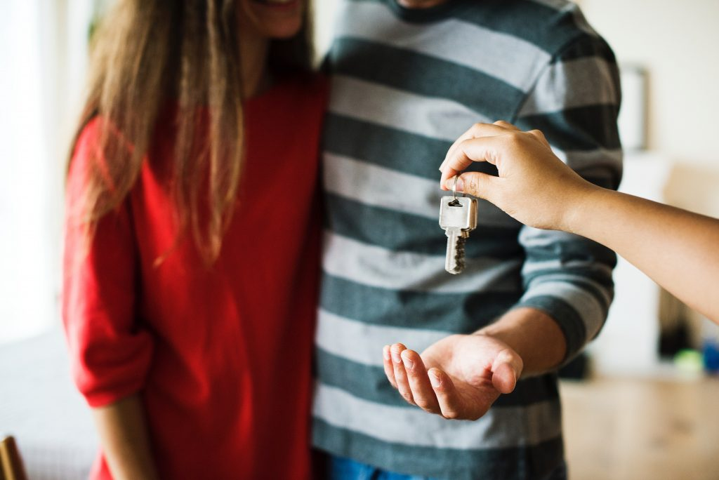 Couple receiving key for their new home.
