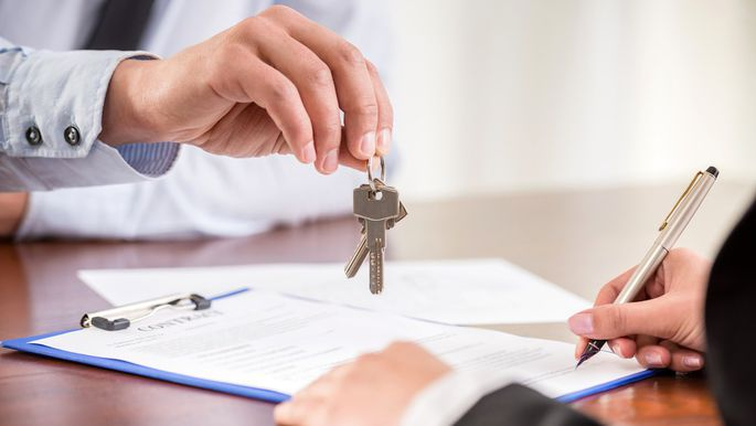 Signing papers while keys are being handed to the person signing